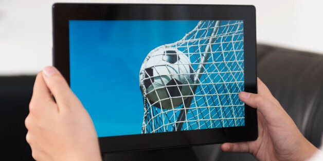 Concept of streaming live sports events. Soccer ball hits the net on a digital