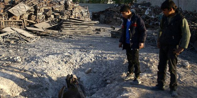 A boy reacts at a damaged site in the town of Hamoria, eastern Ghouta in Damascus, Syria, November 29,...