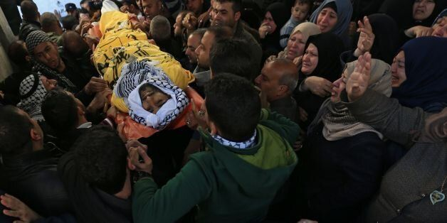 Palestinian mourners carry the body of Mahmoud al-Masri, a 30-year-old Palestinian man who was killed...