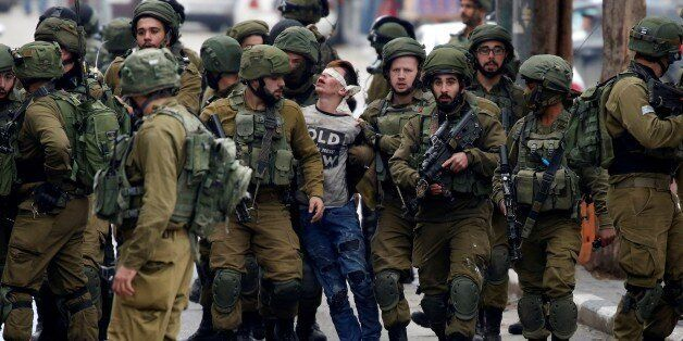 HEBRON, WEST BANK - DECEMBER 7 : Israeli forces detain Palestinian Fevzi El-Junidi, 14-year-old, following...