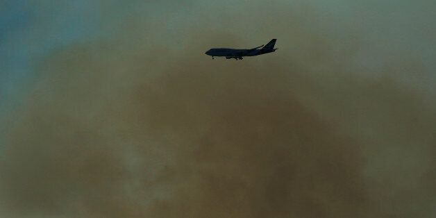 A Qantas Boeing 747 prepares to land at Sydney International Airport through smoke caused by a bushfire...