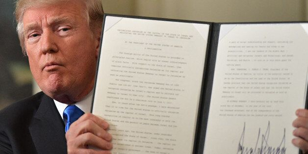 US President Donald Trump holds up a signed memorandum after he delivered a statement on Jerusalem from...