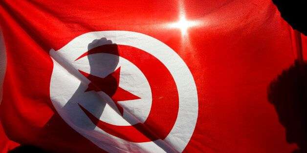 Tunisian people living in France demonstrate behind the Tunisian national flag during a protest in Marseille...