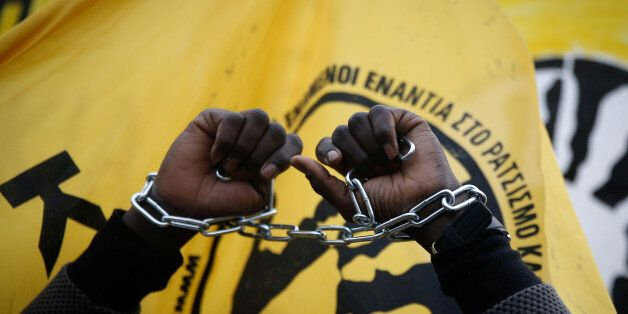 An African migrant living in Greece raises his chained hands during a protest against recent reports...