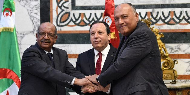 Tunisian Foreign Minister Khemaies Jhinaoui (C) holds hands with his Algerian counterpart Abdelkader...