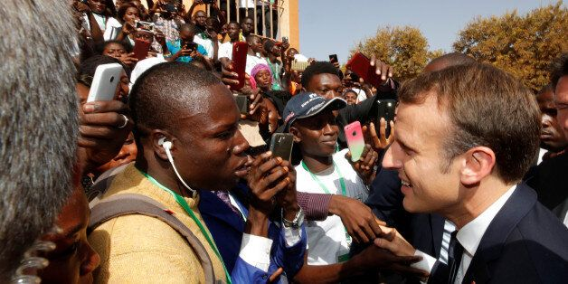 French President Emmanuel Macron shakes hands with people in the crowd as he leaves the Ouagadougou University,...