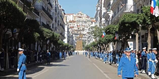 Algerian police stand guard in the street in Algiers during a visit by the French president on December...
