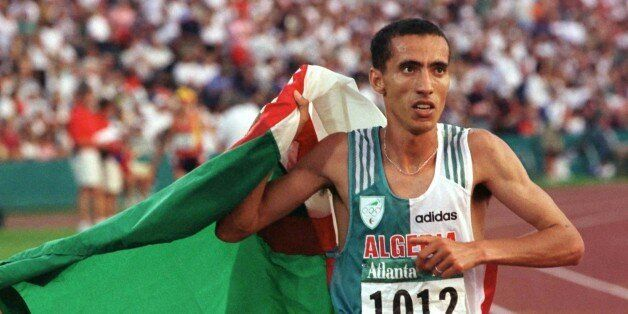 Noureddine Morceli carries the Algerian flag in a victory lap as he celebrates his gold medal win in...