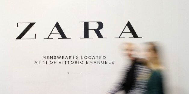 People walk in front of an advertisement for an Inditex owned Zara store in Milan, Italy, March 30, 2017....