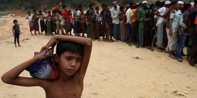 Rohingya refugees wait for the start of relief aid distribution at Balukhali refugee settlement, near...