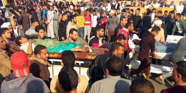 TOPSHOT - Egyptians carry victims on stretchers following a gun and bombing attack on the Rawda mosque...