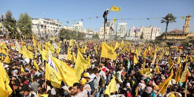 Fatah supporters wave the party flag as they take part in a rally in Gaza City on November 11, 2017....