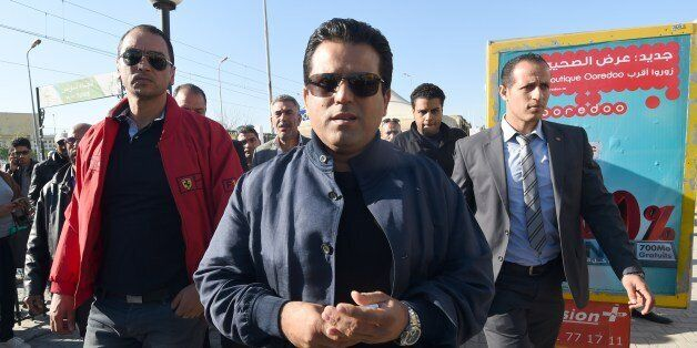 Tunisian presidential candidate and founder of the Free Patriotic Union Slim Riahi (C) arrives at a bus...