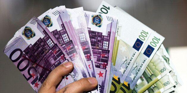 An activist shows fake banknotes during a demonstration outside the European Commission (EC) headquarters...