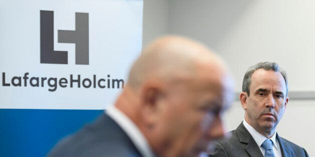 Outgoing CEO of the French-Swiss construction materials giant LafargeHolcim, Eric Olsen (R) listens to...