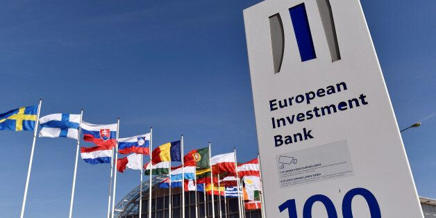 Flags are seen behind the logo of the European Investment Bank is pictured in the city of Luxembourg,...