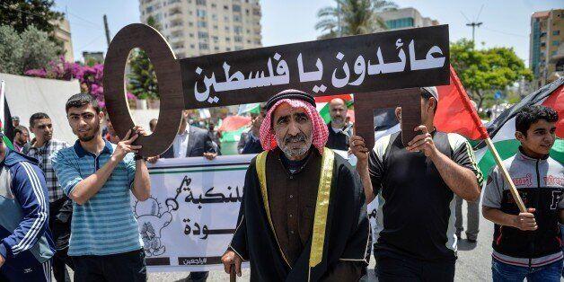 GAZA CITY, GAZA - MAY 15 : Palestinian men hold banners and keys symbolize the Palestinian settlements...