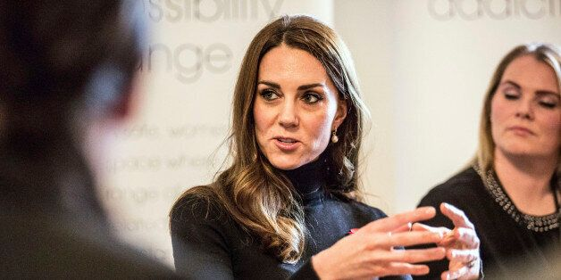 Catherine, Duchess of Cambridge speaks with staff members during a visit to the Nelson trust women's...