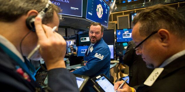 Traders work on the floor of the New York Stock Exchange (NYSE) in New York, U.S., on Monday, Oct. 16,...