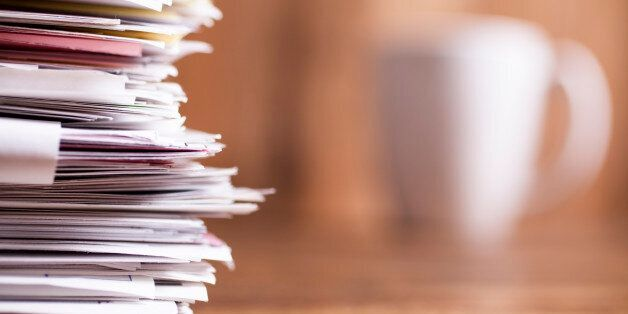 Large stack of multi-colored files and paperwork lie on an office desk. A white coffee mug in background....