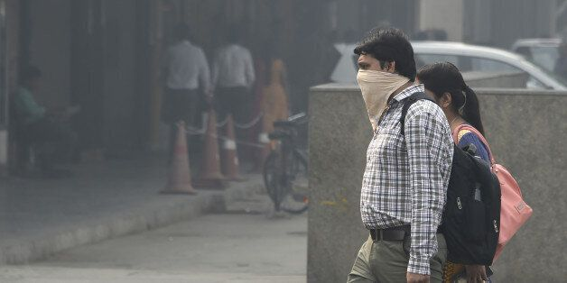 An Indian pedestrian protects his face in heavy smog in New Delhi on October 20, 2017 the day after the...