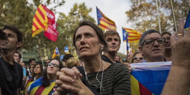 Pro independence supporters react as they wait outside the Catalan parliament for the result of a vote...
