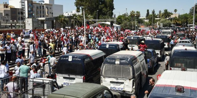 Members of the Tunisian security forces block the road with vehicles along Bardo Square, outside parliament...