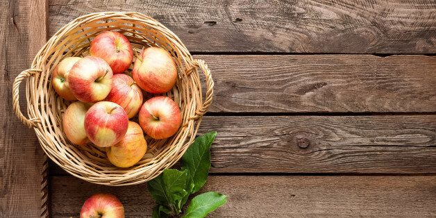 fresh apples in wicker basket on wooden