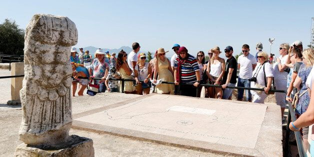 Tourists listen to their guide during their visit to the archaeological site of Carthage, near Tunis,...