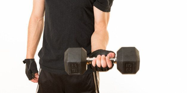 TORONTO, ONTARIO, CANADA - 2012/03/24: Healthy habits: Young adult exercising with a 25 pounds weight....