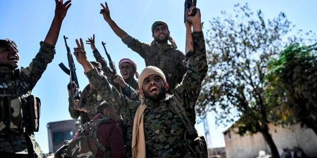TOPSHOT - Members of the Syrian Democratic Forces (SDF), backed by US special forces, celebrate at the...