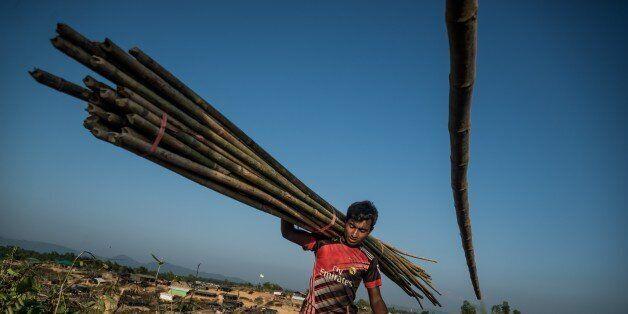 COXS BAZAR, BANGLADESH - OCTOBER 27: A Rohingya Muslim carries bamboo logs at Kutupalong Rohingya refugee...