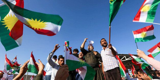 Iraqi Kurds wave flags of Iraqi Kurdistan and shout slogans during a demonstration outside the UN Office...