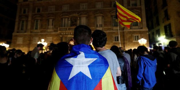 A man wears an Estelada, Catalan separatist flag, as protesters gathered outside the regional government...
