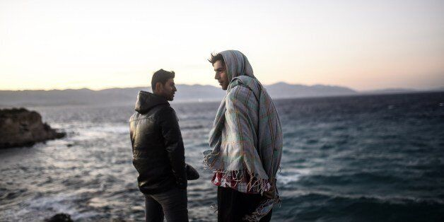 Young men look towards the Greek Chios island as they wait for the wind to calm down to travel on a dinghy...