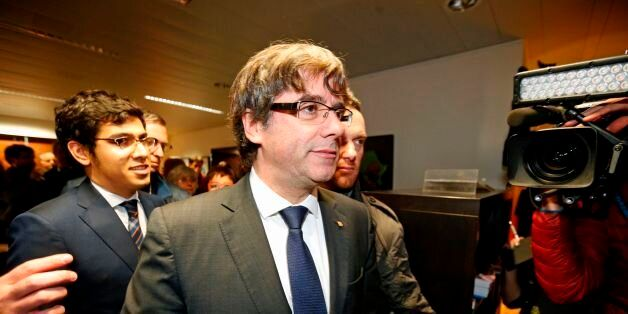Dismissed Catalonia's leader Carles Puigdemont (C) arrives to address media representatives at The Press...