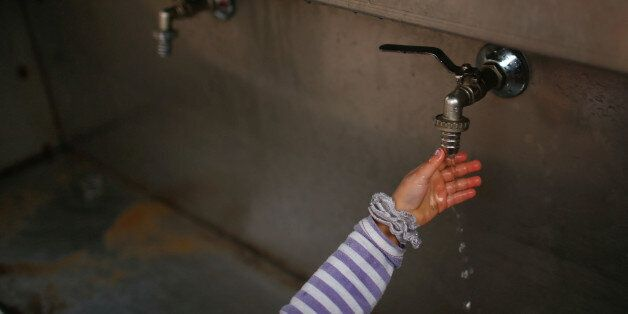 A Palestinian girl uses a public tap to wash her hand in Jabaliya refugee camp in the northern Gaza Strip...