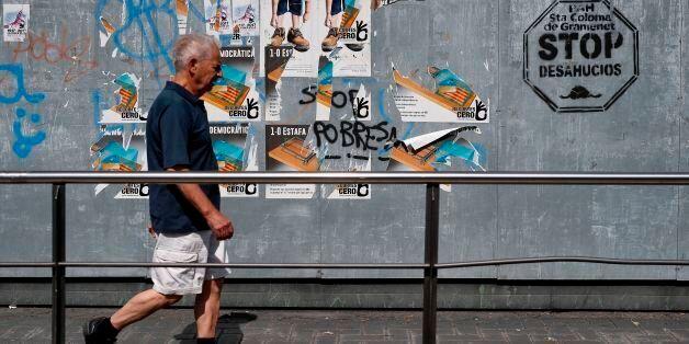 A man walks in front of pro-referendum posters in Santa Coloma de Gramenet on September 16, 2017. / AFP...