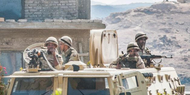 Aswan, Egypt - March 5, 2015: Four soldiers, flagging badly, try not to let the heat and the boredom...