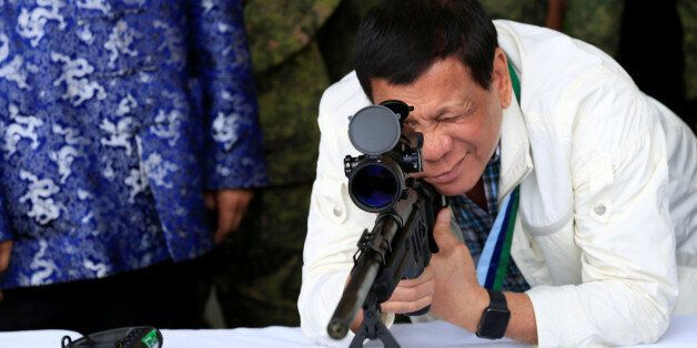 Philippine President Rodrigo Duterte checks the scope of a 7.62mm sniper rifle during the turnover ceremony...