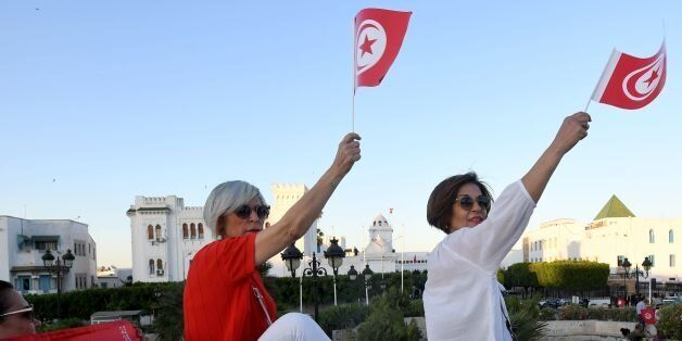 Tunisians hold flags during a demonstration in solidarity with Prime Minister Youssef Chahed in his fight...