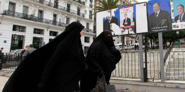 Algerian women walk past electoral posters in Algiers, April 2, 2014. Campaigning began on March 23 for...