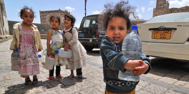 YEMEN, SANA - MAR 6, 2010: Unidentified girls with empty water-pots going in search of drinking water...