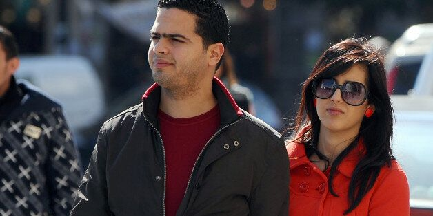 A Tunisian couple walks in Habib Bourguiba Avenue on February 28, 2012 in Tunis. The Association Tunisian...