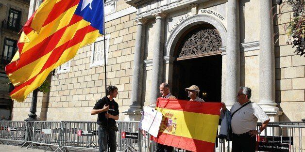 BARCELONA, SPAIN - OCTOBER 30: Some people unfold a Spanish flag as another man waves a Catalan pro-independece...