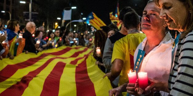 BARCELONA, SPAIN - 2017/10/17: A large flag of Catalonia is seen surrounded by demonstrators holding...