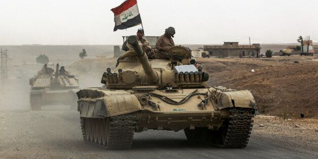 Iraqi soldiers ride atop the turret of a Russian-made T-72 tank, as Iraqi forces advance towards the...