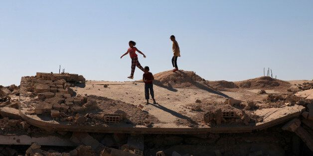 Syrian children are seen playing on a damaged house in Bosra al Sham town, south of Deraa, Syria October...