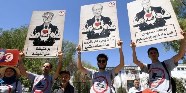 Tunisians chant slogans, wear t-shirts reading in the local Arabic dialect 'I am not forgiving', and...