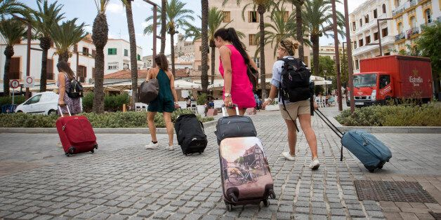 Tourists pull their suitcases in the port of Ibiza, on August 11, 2017.Known as much as a wild party...